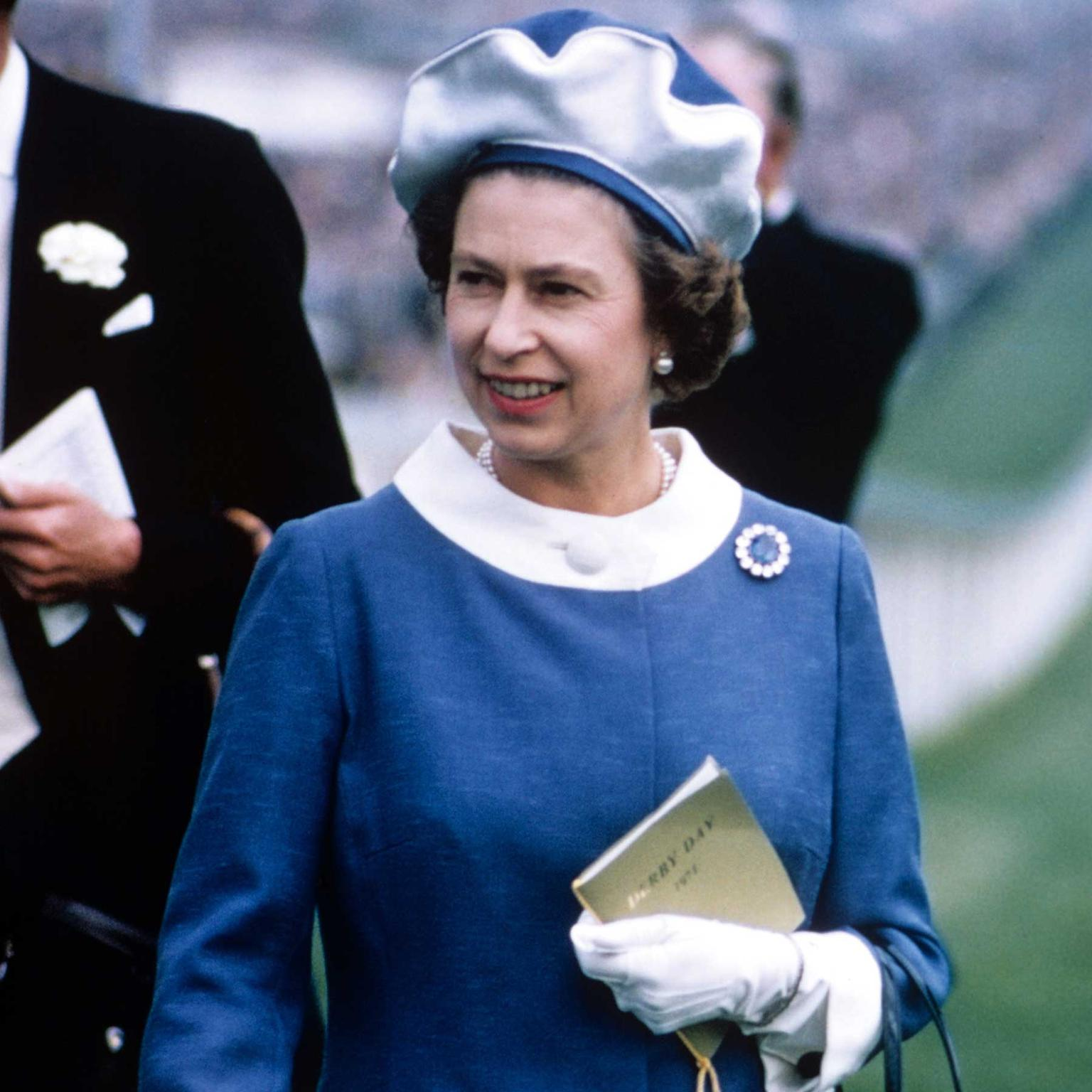 Queen Elizabeth II wearing the sapphire brooch that Princess Diana's engagement ring resembled. (Photo credit: Getty Images)